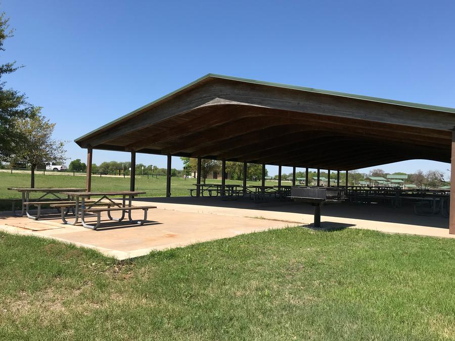 Grill located in Group Shelter area with a restroom in the distance