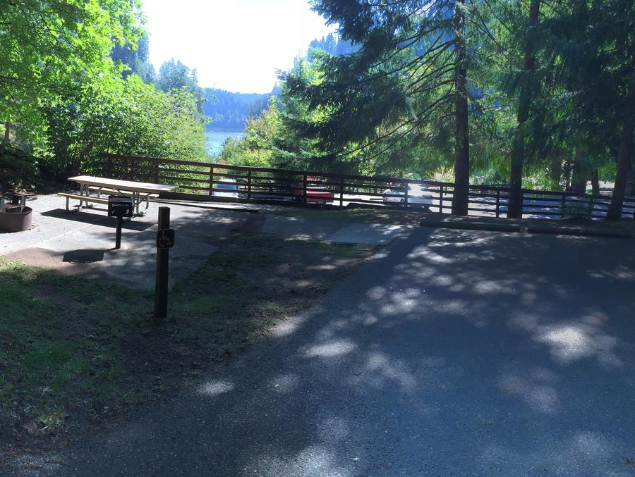 Picture of barrier free (accessable ) site with picnic table, fire ring, BBQ grill and tent pad.