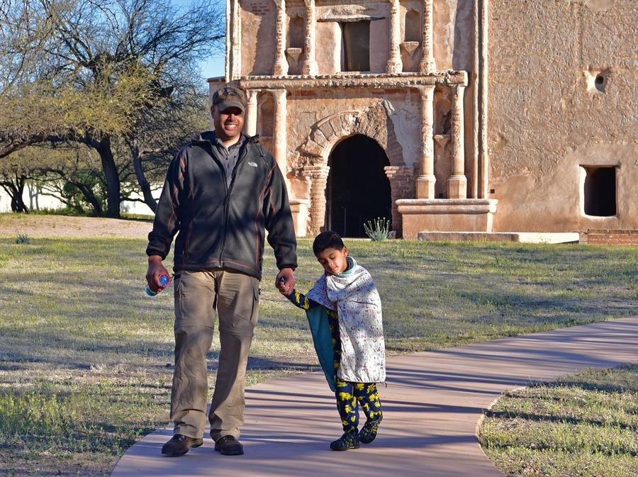 Boy and father in front of mission churchMorning breaks and campers climb out of their beds for hot empanadas, coffee, and chocolate.