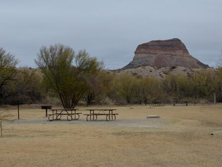 Flat, grassy campsite with desert bluff in the backgroundFlat, grassy campsite
