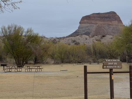 Group campsite sits among the desert brush in a fenced in area with a desert bluff in the backgroundCampsite and picnic tables sit among the desert brush in a fenced in area