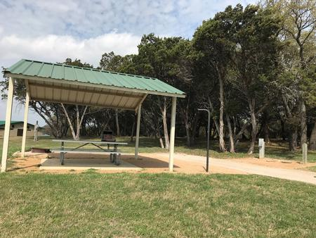 RV site with covered picnic table, grill, fire ring, and restroom/shower facilites nearby