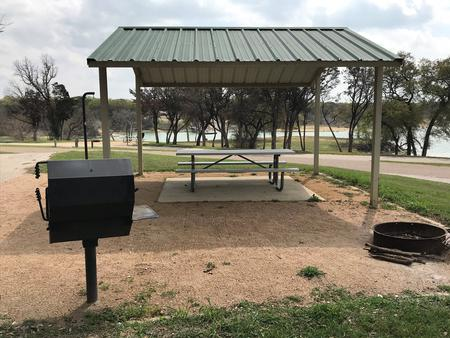 Grill, fire ring, and covered picnic table with Waco Lake in the background