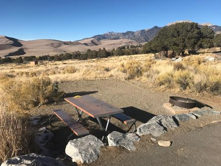 Closeup view of Site #36 designated tent pad, picnic table and fire ring. Sand Dunes in the background.Site #36, Pinon Flats Campground