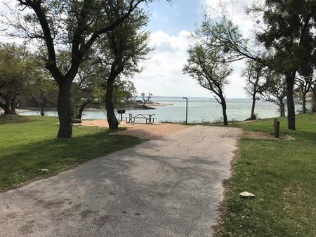 RV site with picnic table, grill, fire ring, and view of Waco Lake