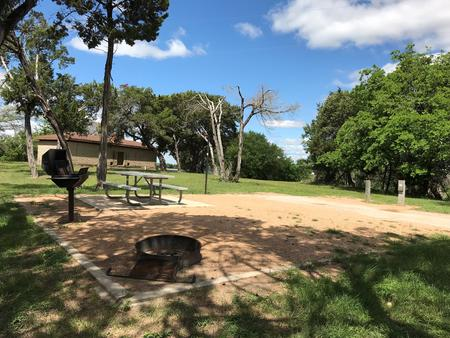 Picnic table, grill, and fire ring with restroom/shower facilities in the background