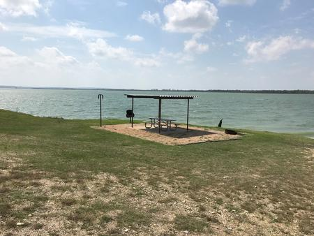 Tent site with picnic table, grill, and fire ring.  Site is located very close to shoreline of Waco Lake