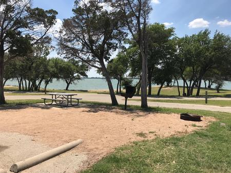 Picnic table, grill, and fire ring with Waco Lake in the background