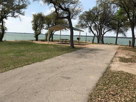 RV site with covered picnic table, grill, and fire ring with great view of Waco Lake