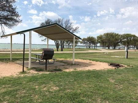 Covered picnic table, grill, fire ring, and Waco Lake in the background