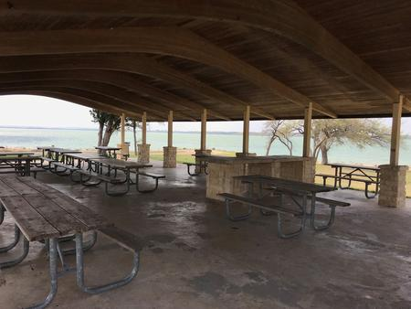 Picnic tables under the pavilion with Waco Lake in background