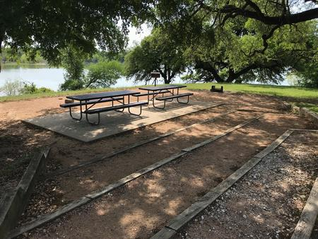 Picnic tables, grill, and fire ring with Waco Lake in the background