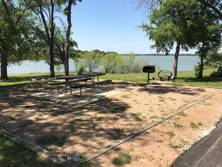Picnic table, grill, and fire ring at site with great view of Waco Lake
