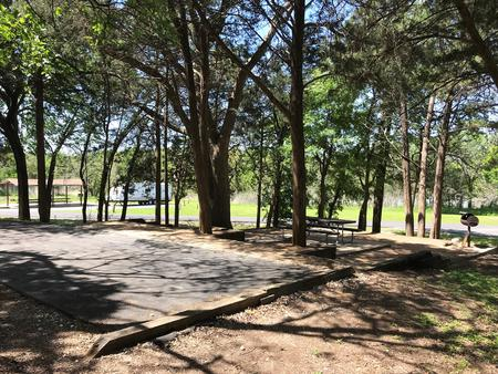RV site with picnic table, grill, and fire ring