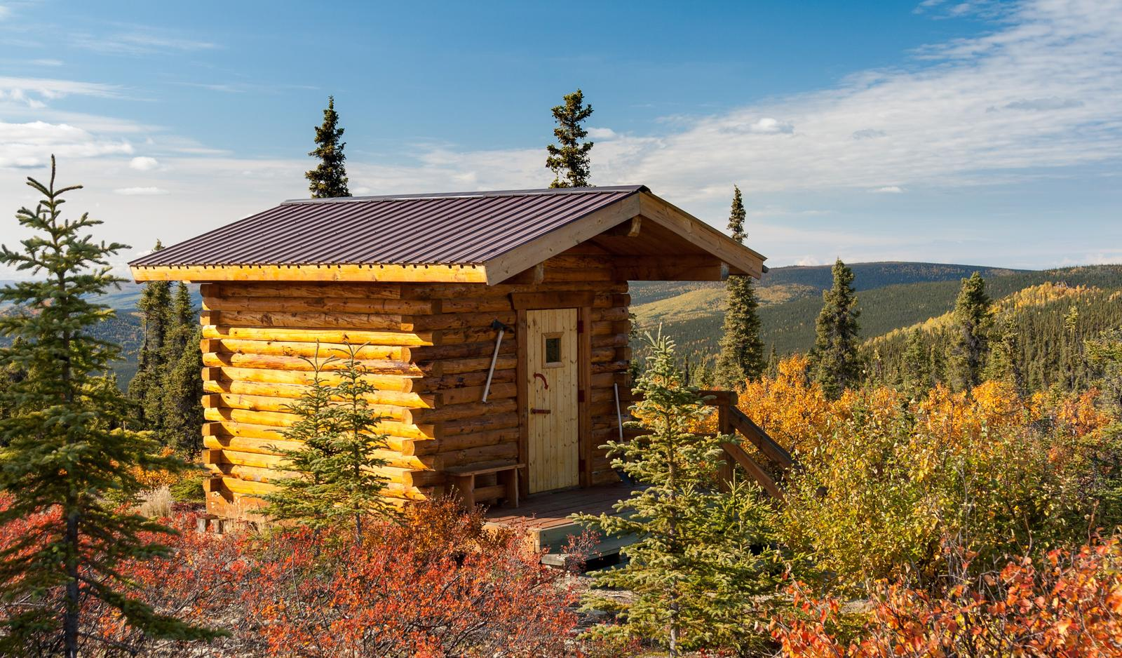 A small cabin sits on a ridge surrounded by fall foliageSummit Trail Shelter on a sunny fall day