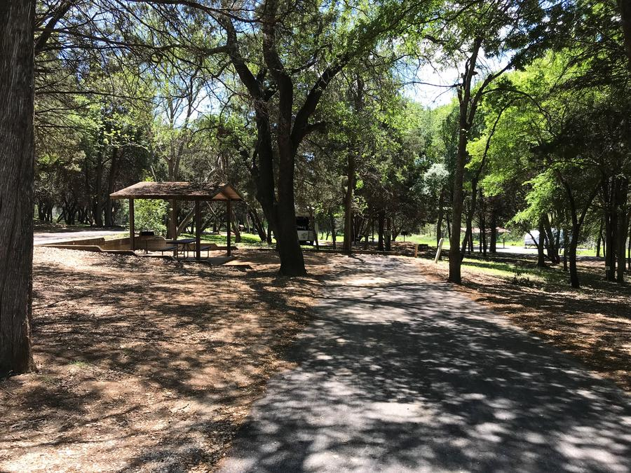RV site with covered picnic table, grill, and fire ring