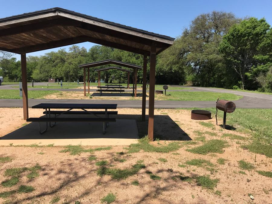 Covered picnic table, grill, and fire ring with other sites nearby