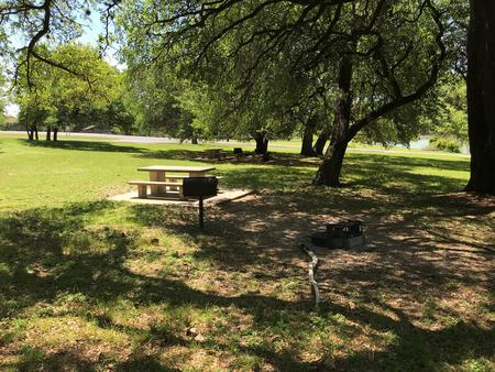 Tent site with picnic table, grill, and fire ring