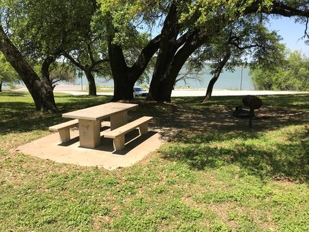 Tent site with picnic table, grill, and fire ring with Waco Lake in the background