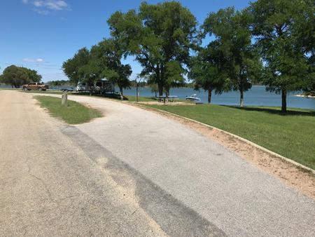 Pull through RV site with picnic table, grill, fire ring, and Waco Lake in the background