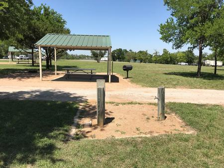 Covered picnic table, grill, and fire ring at site with Waco Lake in the background
