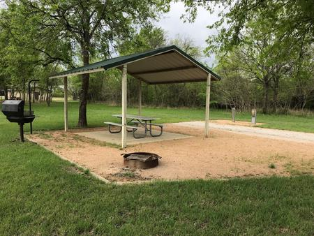 RV site with covered picnic table, grill, and fire ring.  Site is close to restroom/shower facilities