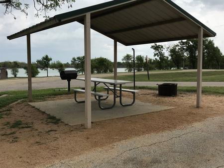 Covered picnic table, grill, and fire ring with Waco Lake in the background