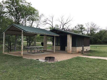 Screen shelter with covered picnic table, grill, and fire ring