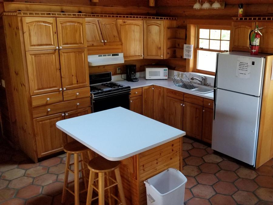 View of the kitchen in the Hillside Cabin with wood cabinents refrig, stove, and island bar with 2 stoolsHillside Cabin kitchen