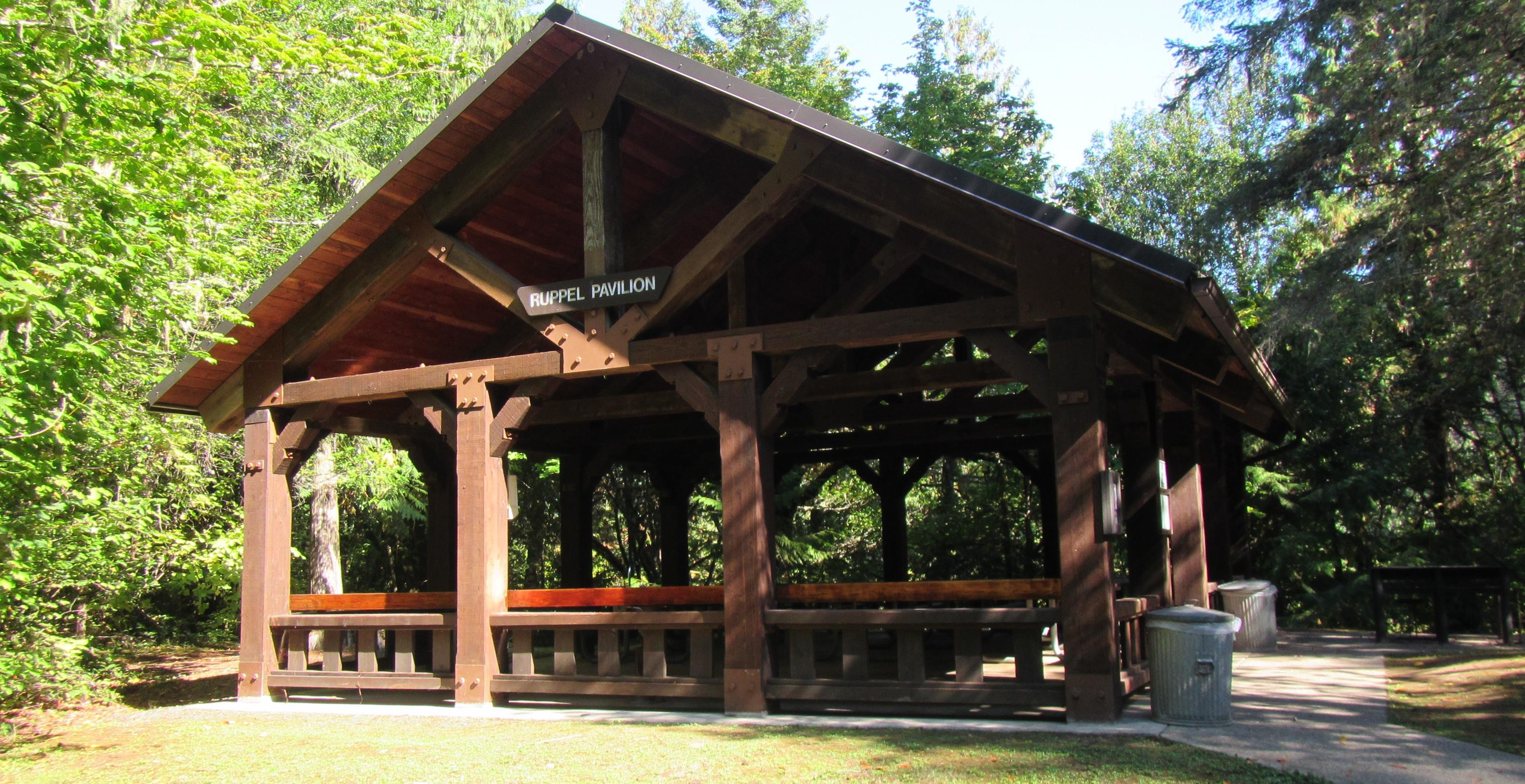 Large wooden pavilion, surrounded by trees and grass