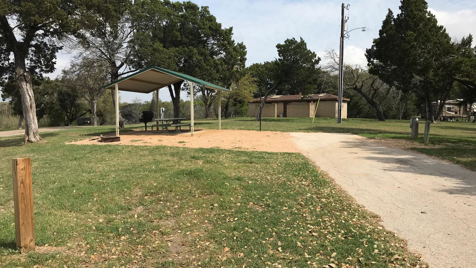 RV site with grill, fire ring, covered picnic table, and restroom/shower facilities nearby
