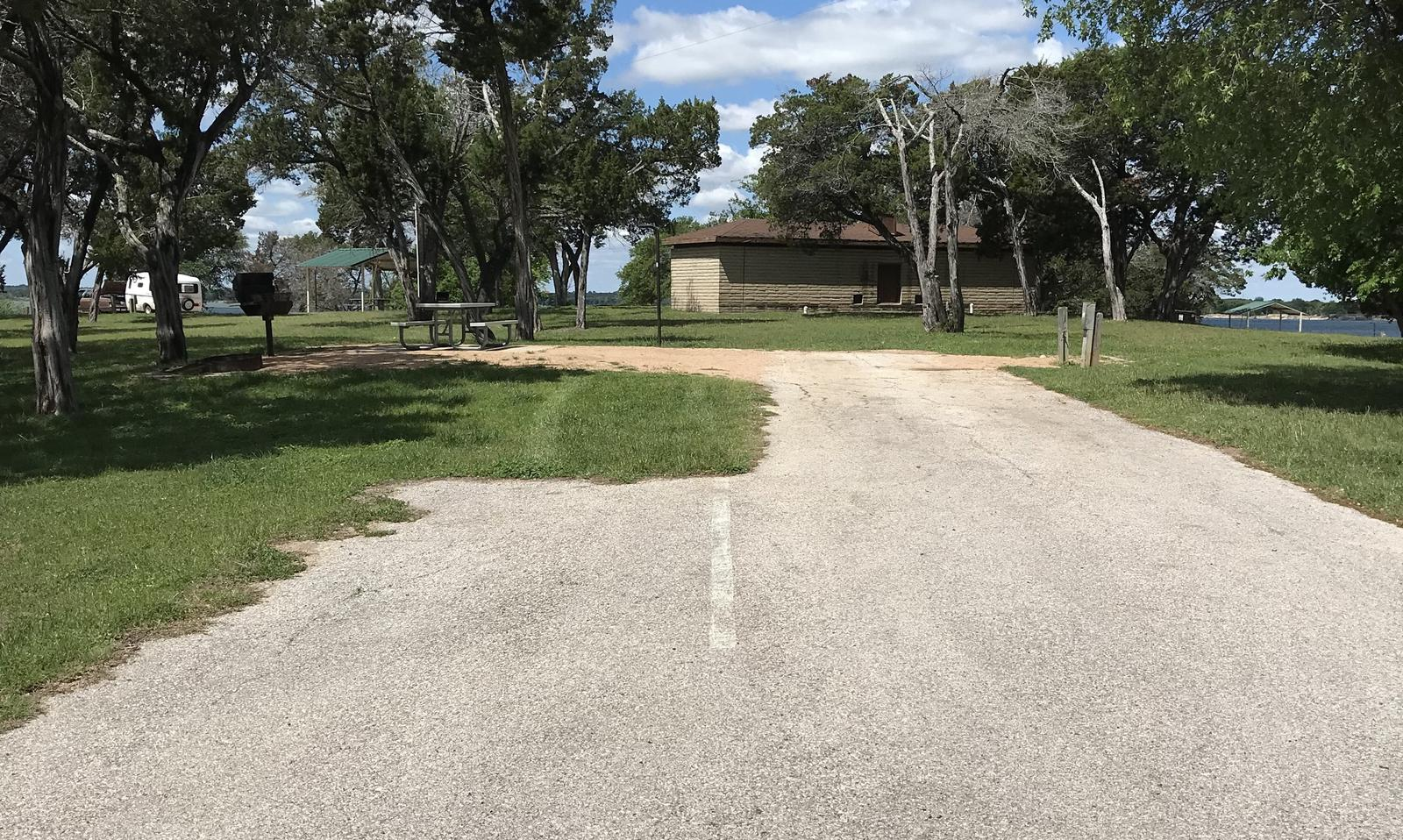 RV site with grill, fire ring, picnic table, and restroom/shower facilities nearby
