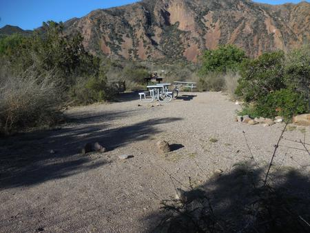 Flat, gravel area and picnic tables in the site, with mountains in the backgroundFlat, gravel area and picnic tables
