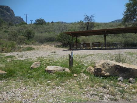 Rocks delineating the site with the shade structure and picnic tables visible behindShade structure with picnic tables and bear boxes