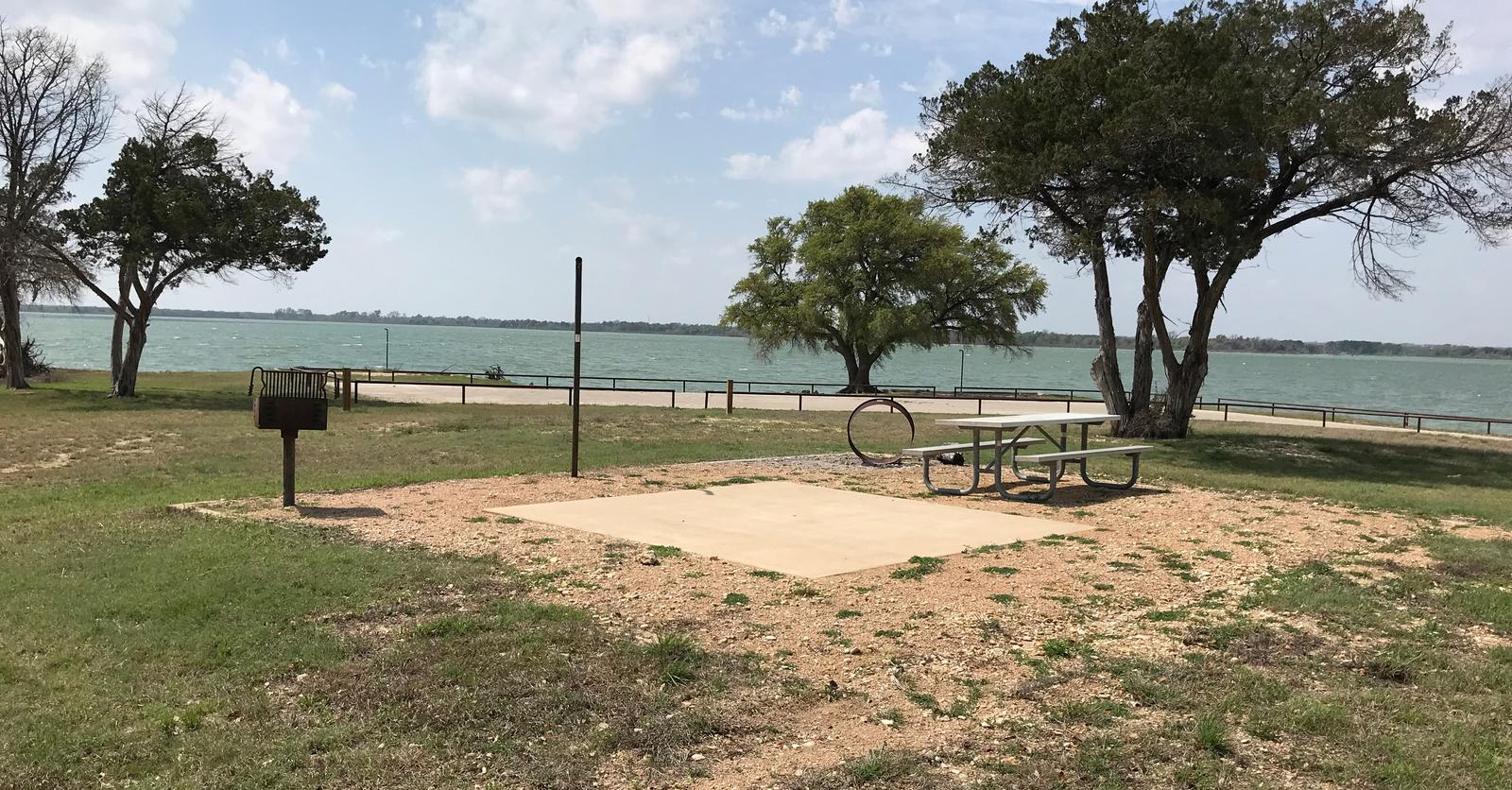 Tent site with picnic table, grill, fire ring, and Waco Lake in the background