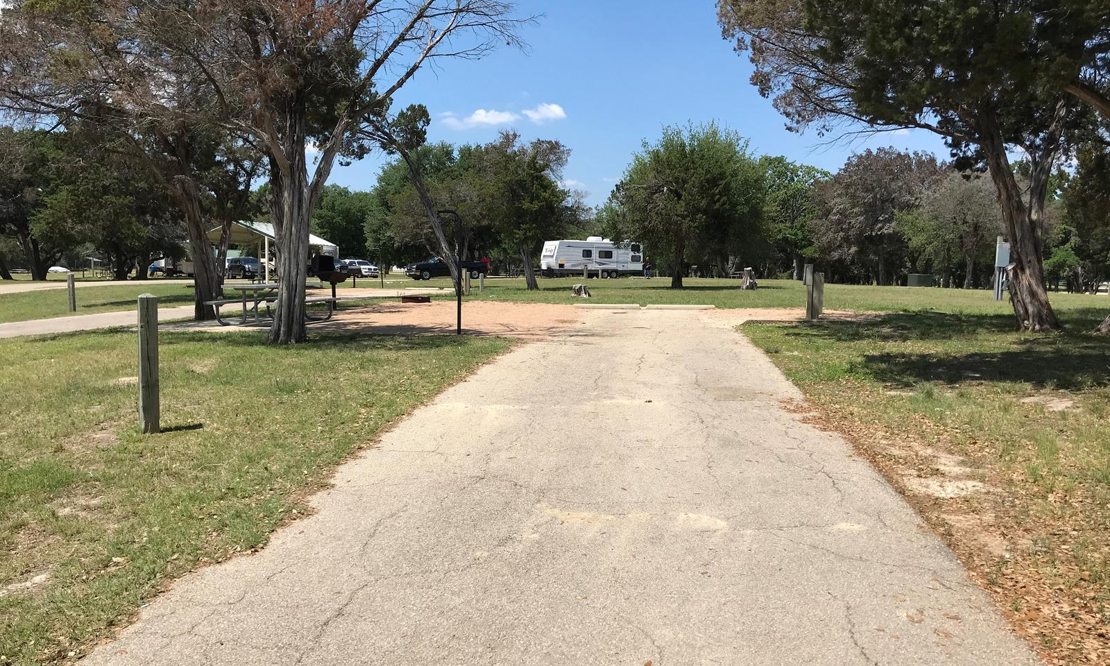 RV site with picnic table, grill, and fire ring.