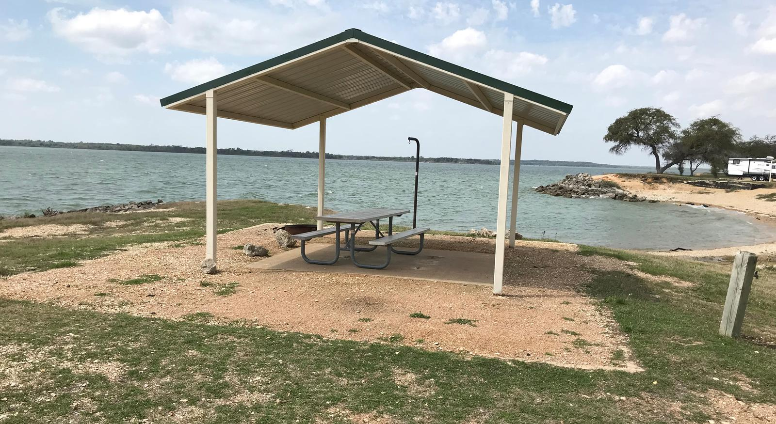Tent site with covered picnic table and fire ring.  Site is located very close to shoreline of Waco Lake