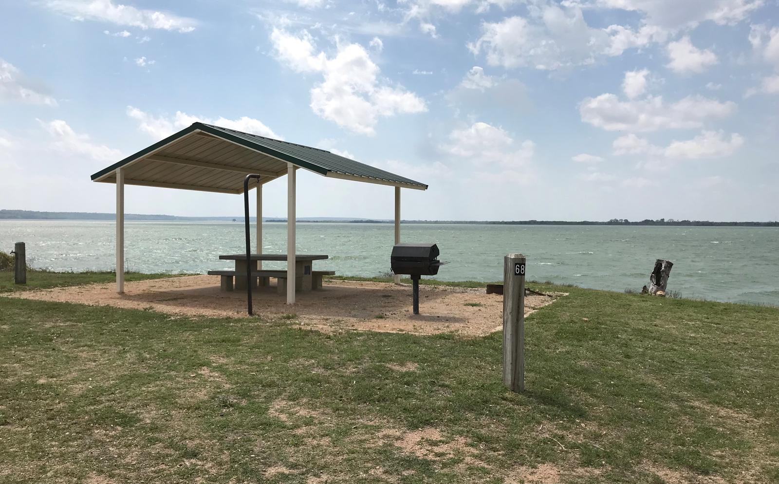 Tent site with covered picnic table, grill, and fire ring.  Site is located very close to shoreline of Waco Lake