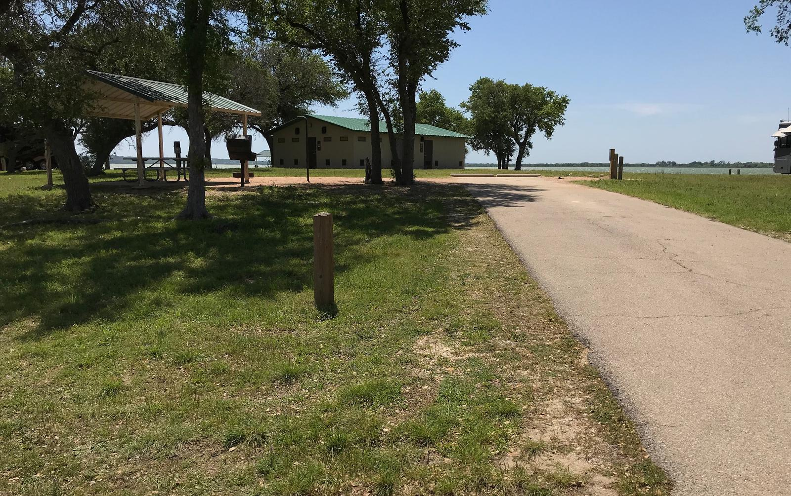 RV site with covered picnic table, grill, fire ring, and restroom/shower facilities nearby