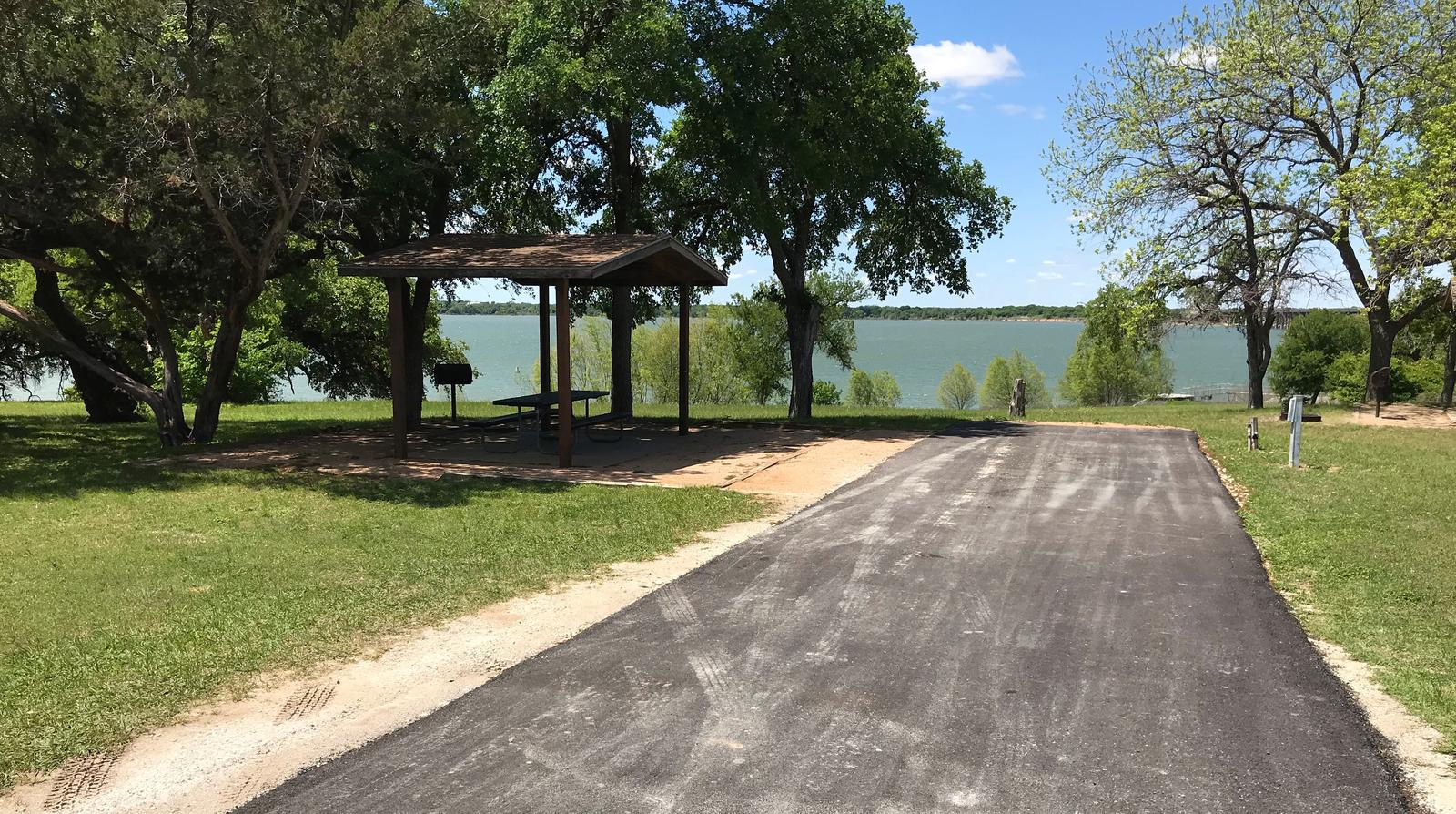 RV site with covered picnic table, grill, fire ring, and Waco Lake in the background