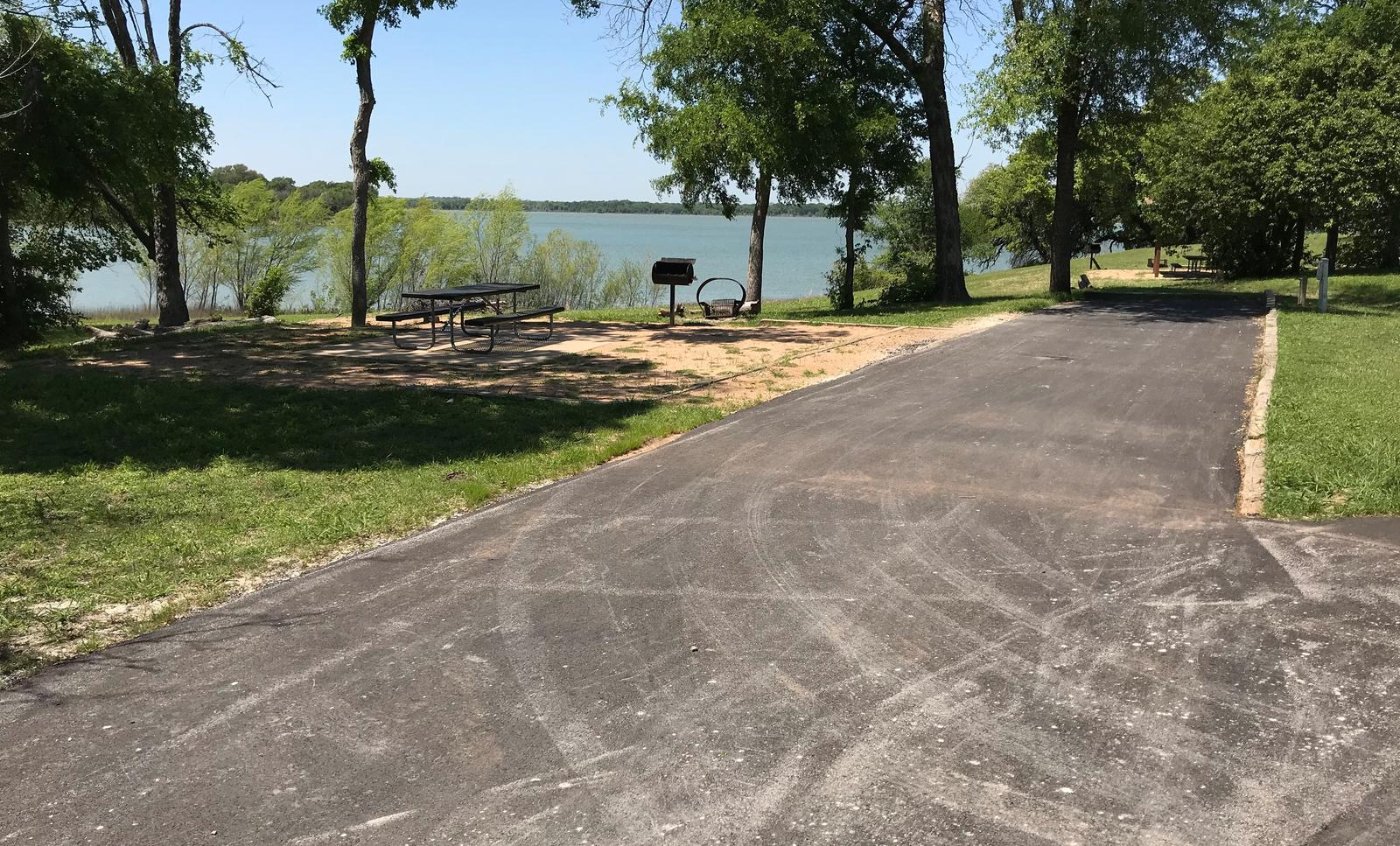 RV site with picnic table, grill, fire ring, and Waco Lake in the background Ca