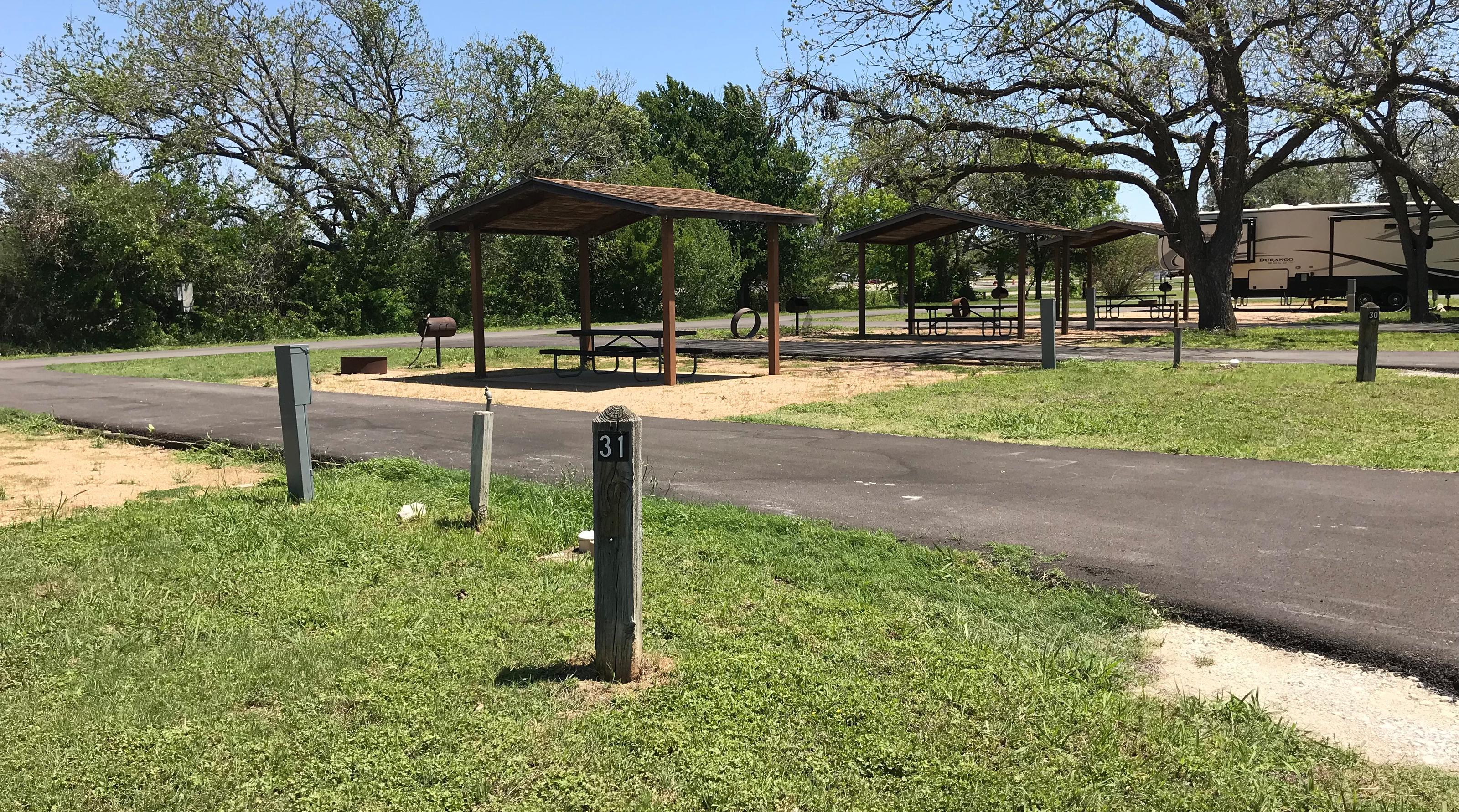 Pull through RV site with covered picnic table, grill, and fire ring