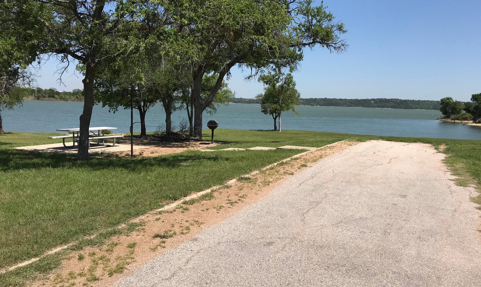 RV site with picnic table, grill, fire ring, and Waco Lake in the background