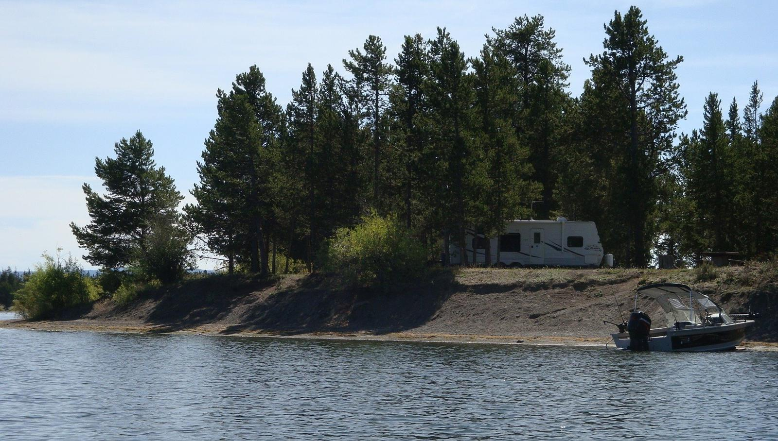 View of Lonesomehurst Campground from Hebgen Lake, boat, RV & pine treesLonesomehurst Campground