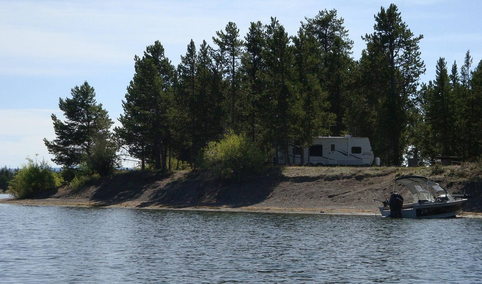 View from Hebgen Lake - Lake, boat and RV surrounded by pine treesLonesomehurst Campground