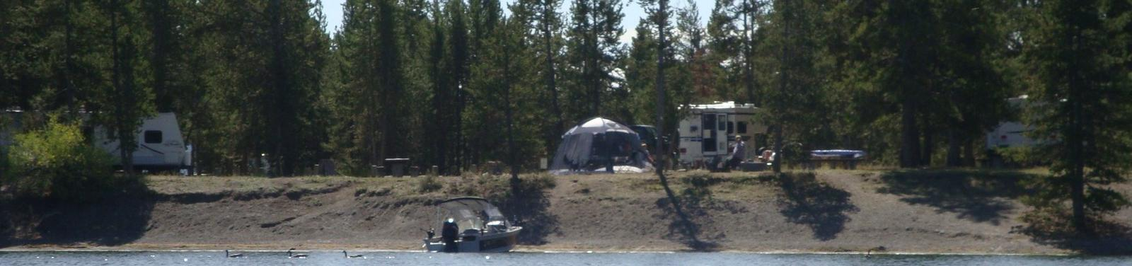 View of Lonesomehurst Campground from Hebgen Lake, boat, RV, tent  & pine treesLonesomehurst Campground
