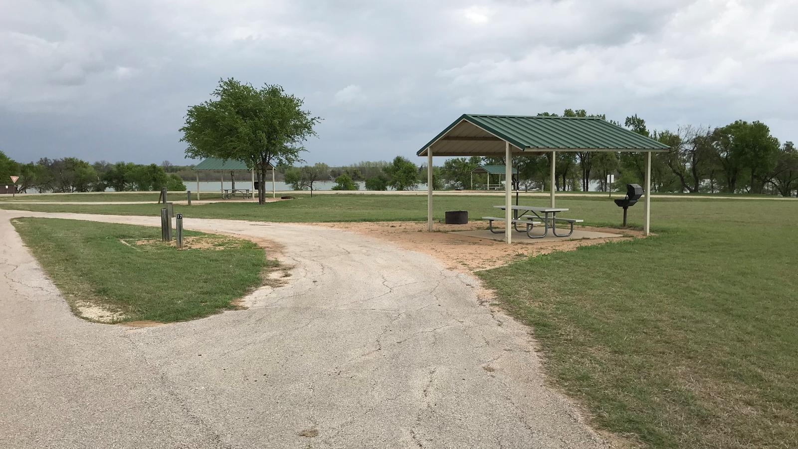 Pull through RV site with covered picnic table, grill, fire ring, and Waco Lake in the background