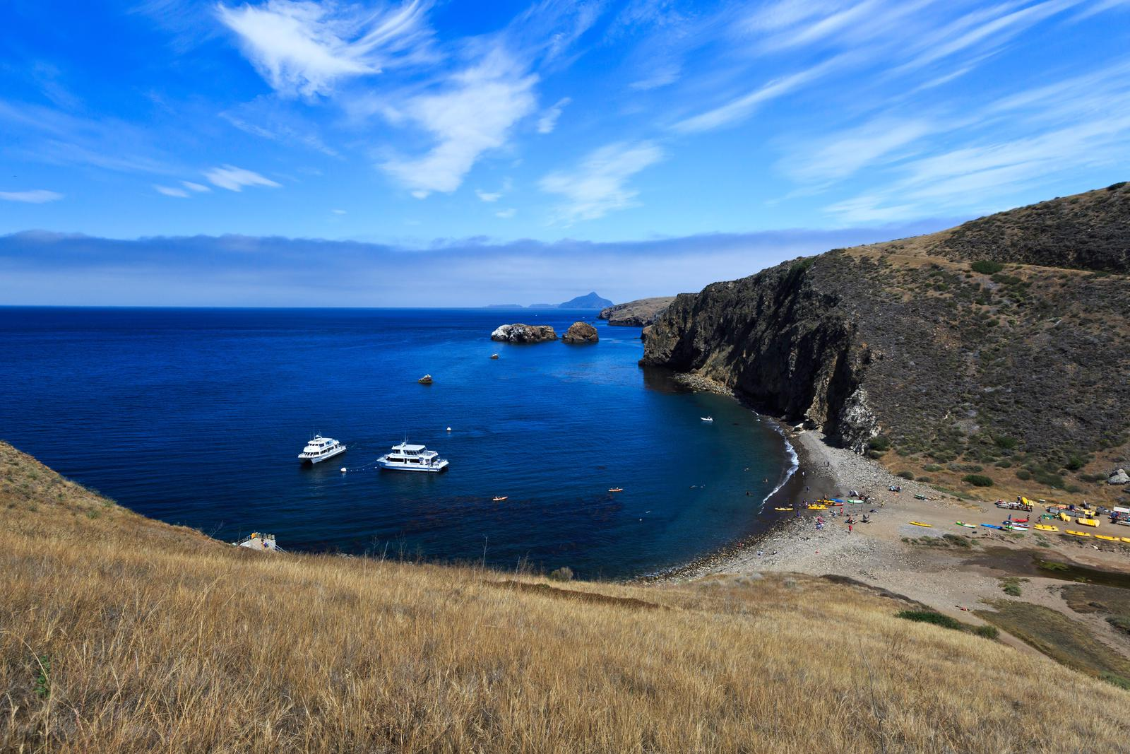 Harbor with boats, kayaks, and visitors on the beach. Steep island cliffs and other islands in the distance. Scorpion Anchorage, Santa Cruz Island