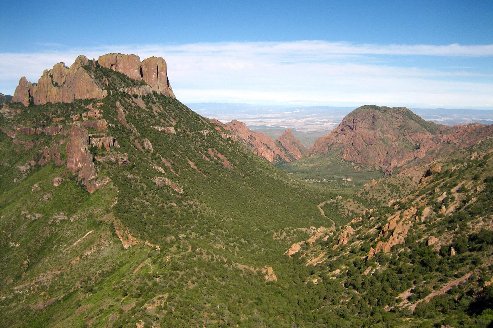 View of Chisos Basin from the Lost Mine trail. Green vegetation with red mountainsView of Chisos Basin from the Lost Mine trail