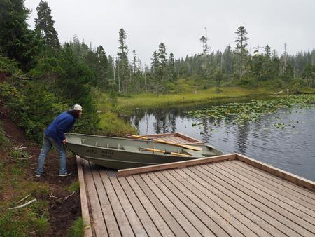 Person pushing skiff into lake from platformSkiff at Middle Ridge Cabin
